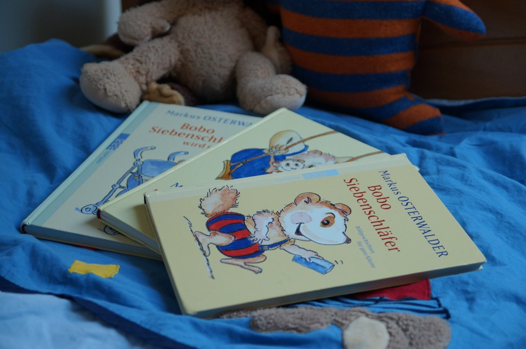 Our collection of Bobo Siebenschläfer books on our four-year-old son's bed.